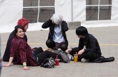 Grupo de visitantes que se sientan en la tierra en Animefest Fotos de archivo