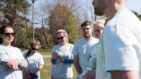 Grupo de voluntários que escutam o mentor no parque video estoque