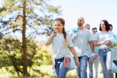Grupo de voluntarios con los bolsos de basura en parque foto de archivo libre de regalías