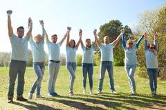 Grupo de voluntarios felices que llevan a cabo las manos al aire libre Fotos de archivo libres de regalías