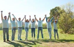 Grupo de voluntarios felices que llevan a cabo las manos al aire libre Foto de archivo libre de regalías