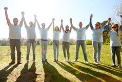 Grupo de voluntarios felices que llevan a cabo las manos al aire libre Imagenes de archivo