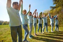 Grupo de voluntarios felices que llevan a cabo las manos al aire libre Fotografía de archivo libre de regalías