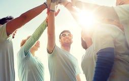 Grupo de voluntarios que hacen el alto cinco al aire libre imagenes de archivo