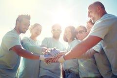Grupo de voluntarios que ponen las manos en el top al aire libre Fotos de archivo