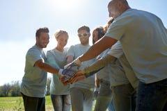 Grupo de voluntarios que ponen las manos en el top al aire libre Foto de archivo