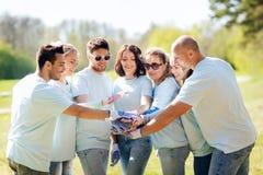 Grupo de voluntarios que ponen las manos en el top en parque Foto de archivo