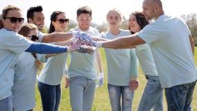 Grupo de voluntarios que ponen las manos en el top en parque almacen de metraje de vídeo