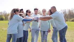 Grupo de voluntarios que ponen las manos en el top en parque almacen de video