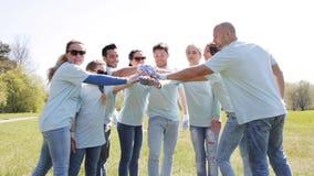 Grupo de voluntarios que ponen las manos en el top en parque metrajes