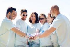 Grupo de voluntarios que ponen las manos en el top en parque Fotografía de archivo libre de regalías