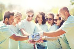 Grupo de voluntarios que ponen las manos en el top en parque Imágenes de archivo libres de regalías
