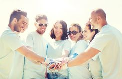 Grupo de voluntarios que ponen las manos en el top en parque Imagenes de archivo