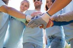 Grupo de voluntarios que ponen las manos en el top en parque Fotografía de archivo