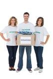 Grupo de voluntarios que sostienen la caja de la donación con ropa Fotografía de archivo