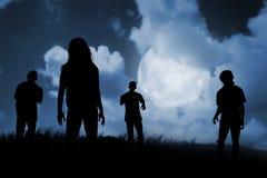 Grupo de zombi que anda na noite Imagens de Stock