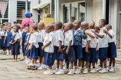 Grupo del africano de alumnos jovenes pre que bailan y que cantan en el patio de la escuela, Matadi, Congo, África central fotografía de archivo libre de regalías