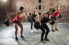 Grupo del gimnasio con entrenamiento del levantamiento de pesas fotografía de archivo libre de regalías
