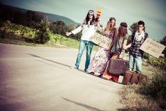 Grupo del Hippie que hace autostop en un camino del campo Foto de archivo libre de regalías