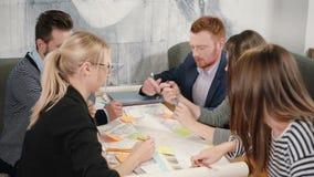 Grupo del intercambio de ideas de reunión creativa del equipo de la pequeña empresa de los arquitectos jovenes en oficina de lanz metrajes