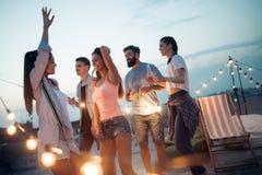 Grupo despreocupado de amigos felices que disfrutan del partido en terraza del tejado foto de archivo libre de regalías