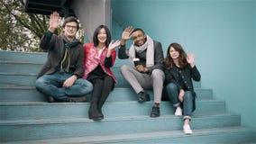 Grupo diverso de amigos que acenam as m?os que sentam escadas da OU video estoque