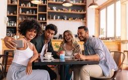Grupo diverso de amigos que toman el selfie en el teléfono elegante en el café imágenes de archivo libres de regalías