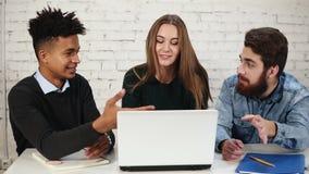 Grupo diverso de empresários novos que discutem ao sentar-se em torno do portátil branco Estão discutindo o projeto do negócio de video estoque