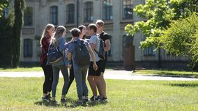 Grupo diverso de estudiantes que recolectan en césped del parque metrajes