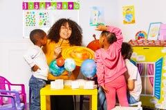 Grupo diverso de los niños aprender los planetas en guardería foto de archivo libre de regalías