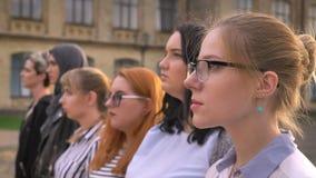 Grupo diverso de meninas caucasianos novas que estão na parte externa do perfil que olha junto afastado vídeos de arquivo