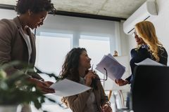 Grupo diverso de mujeres de negocios sonrientes que tienen una rotura en hablar de la oficina imágenes de archivo libres de regalías