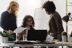 Grupo diverso de mujeres de negocios sonrientes que tienen una rotura en hablar de la oficina imagen de archivo