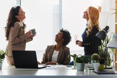Grupo diverso de mujeres de negocios sonrientes que tienen una rotura en hablar de la oficina imagen de archivo libre de regalías