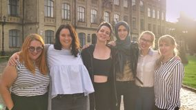 Grupo diverso de rir as meninas caucasianos que estão próximas e que guardam com parte externa orgulhosa no dia vídeos de arquivo