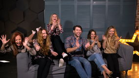 Grupo diverso feliz de amigos que olham esportes na tevê e que cheering em sua equipe no movimento lento vídeos de arquivo