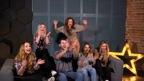 Grupo diverso feliz de amigos que olham esportes na tevê e que cheering em sua equipe no movimento lento filme