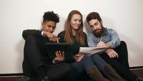 Grupo diverso feliz de estudiantes o de equipo joven del negocio que trabajan en un proyecto Se están sentando en el piso y el tr almacen de metraje de vídeo