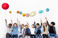 Grupo diverso feliz de niños que sostienen los planetas Imagenes de archivo