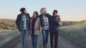 Grupo diverso feliz que anda no trajeto da sujeira filme