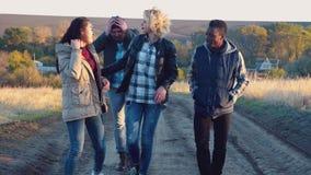 Grupo diverso feliz que anda no trajeto da sujeira video estoque