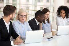 Grupo diverso focalizado sério o de trabalho de fala dos empregados de escritório fotografia de stock royalty free