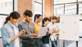 Grupo diverso multiétnico de adulto joven feliz usando los dispositivos del artilugio de la tecnología de la información junto Co Imagen de archivo libre de regalías