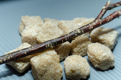 Grupo do açúcar de bastão marrom dos cubos com um ramo Fotos de Stock Royalty Free