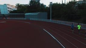 Grupo do atleta da opinião do zangão que corre na trilha do estádio do esporte na noite vídeos de arquivo