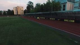 Grupo do atleta da opinião do zangão que movimenta-se na trilha do estádio do esporte na noite filme