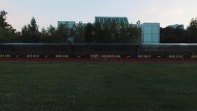 Grupo do atleta da vista aérea que corre na trilha do estádio do esporte na noite filme