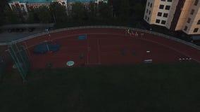 Grupo do atleta da vista aérea que corre na trilha do estádio do esporte na noite vídeos de arquivo
