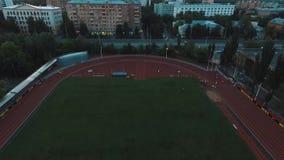 Grupo do atleta da vista aérea que movimenta-se na trilha do estádio do esporte na noite vídeos de arquivo