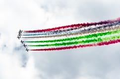 Grupo do avião branco do avião de combate com um traço de fumo colorido contra um céu azul Imagens de Stock Royalty Free